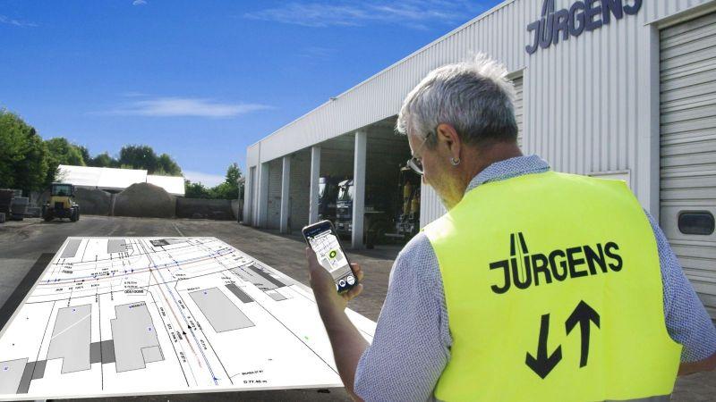 Ein Mitarbeiter der Hermann Jürgens Straßen- und Tiefbauunternehmen GmbH & Co. KG demonstriert die entwickelte App, mit deren Hilfe per Augmented Reality pdf-Baupläne direkt vor Ort an die entsprechende Stelle projiziert werden können.